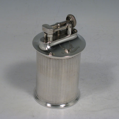 Sterling silver table lighter, having a plain cyclindrical body with engine-turned decoration, and sitting on a flat base. The lighter mechanism is patented (called The Classsic Lighter) and is in fully working order. The dimensions of this fine hand-made silver table lighter are height 9 cms (3.5 inches), diamter 5 cms (2 inches).Please note that this item is crested.
