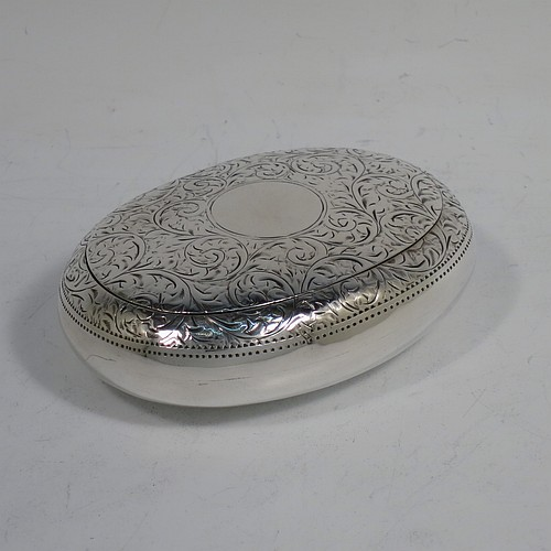 A very pretty Antique Edwardian Sterling Silver tobacco box, having an oval body, with hand-engraved floral and scroll decoration, a vacant cartouche, a squeeze-action sprung hinged lid, and a gold-gilt interior. Made by James Round of Birmingham in 1910. The dimensions of this fine hand-made antique silver tobacco box are length 8 cms (3.25 inches), width 6 cms (2.3 inches), and it weighs approx. 78g (2.5 troy ounces).