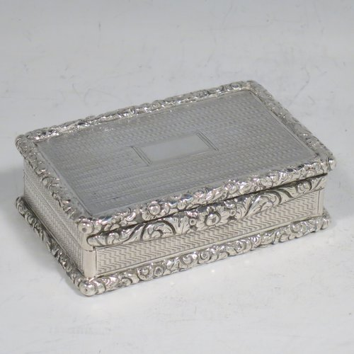An Antique Georgian Sterling silver large and heavy snuff box, having a rectangular body with engine-turned decoration, with applied cast foliate thumb-piece and borders, and a gold-gilt interior. Made by John Bettridge of Birmingham in 1825. The dimensions of this fine hand-made antique silver snuff box are length 8 cms (3.25 inches), width 5 cms (2 inches), depth 2.5 cms (1.0 inches), and it weighs approx. 156g (5 troy ounces).