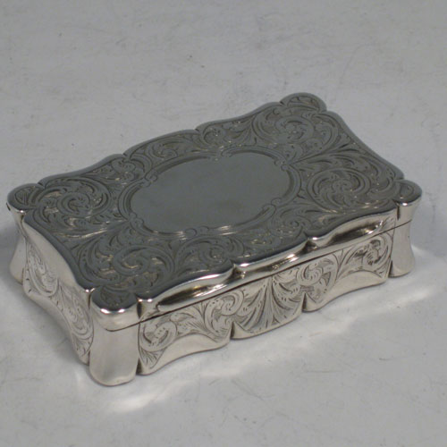 Antique Victorian sterling silver snuff box, having a shaped and hand-engraved body with floral decoration, gold-gilt interior, and hinged lid. Made by Hilliard and Thomason of Birmingham in 1852. Length 7.5 cms (3 inches), height 2 cms (0.75 inches), width 4.5 cms (1.75 inches). Weight approx. 85g (2.7 troy ounces).