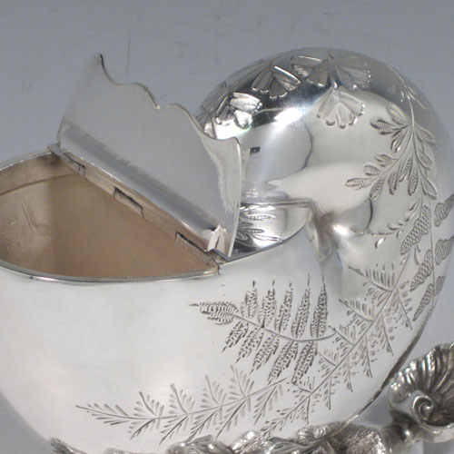 Antique Victorian silver plated spoon warmer, in the shape of a Nautilus shell, having hand-engraved fern-work decoration, a hinged lid, and cast rock base with shell thumb-piece. Made in ca. 1880 with a Victorian makers mark of AB * S. The dimensions of this fine hand-made silver-plated spoon warmer are length 16.5 cms (6.5 inches), height 14 cms (5.5 inches), and width 10 cms (4 inches).