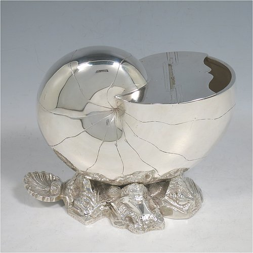 An Antique Victorian Silver Plated spoon warmer, in the shape of a Nautilus shell, having a hand-chased body with invisibly hinged lid opening, and all sitting on a cast rock base with shell thumb-piece. Made by the Atkin Brothers of Sheffield in ca. 1880. The dimensions of this fine hand-made silver-plated spoon warmer are length 16.5 cms (6.5 inches), height 14 cms (5.5 inches), and width 9 cms (3.5 inches).