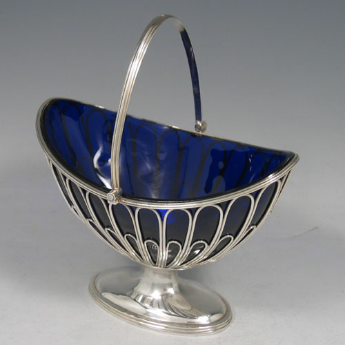 Antique Georgian sterling silver sugar basket, having an oval wire-work body, with hinged reeded swing-handle, a blue-glass liner, and sitting on a pedestal foot. Made by Robert Hennell I of London in 1792. The dimensions of this fine hand-made silver sugar basket are height (inc. handle) 18 cms (7 inches), length 15.5 cms (6 inches), and it weighs approx. 222g (7.2 troy ounces).
