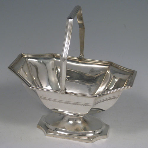 Sterling silver Edwardian sugar basket with hand-egraved octagonal body sitting on a pedestal foot, together with a swing-handle. Made by Ollivant & Botsford of Sheffield in 1910. Height 14.5 cms (5.75 inches), length 13.5 cms (5.25 inches), width 9 cms (3.5 inches). Weight approx. 6 troy ounces (186g).