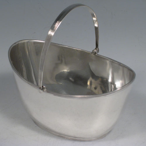 Antique Victorian sterling silver sugar basket, having a plain oval body, with reeded borders, and swing handle. Made by John Hancock and Co., of Sheffield in 1884. Height inc. handle 11 cms (4.25 inches), length 12 cms (4.75 inches), width 9 cms (3.5 inches). Weight approx. 115g (3.7 troy ounces).