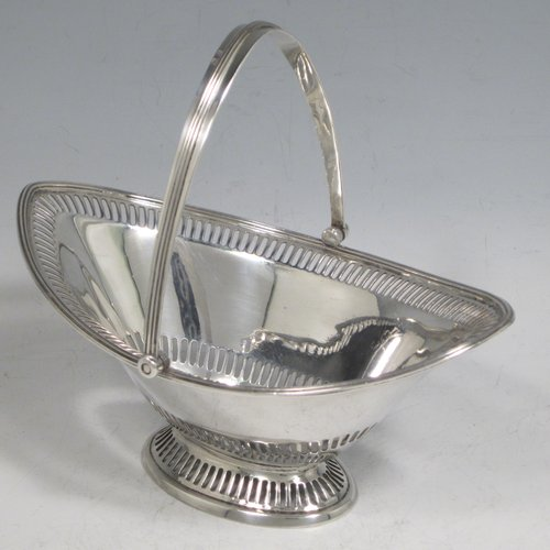 Antique Edwardian sterling silver sugar or sweetmeat basket, having an oval body, with an upper and lower band of hand-pierced decoration, an applied reeded border, a reeded swing-handle, and sitting on a pedestal foot with matching piercing. Made by Walker & Hall of Birmingham in 1910. The dimensions of this fine hand-made silver sugar basket are height 14.5 cms (5.75 inches), length 16.5 cms (6.5 inches), width 11 cms (4.25 inches), and it weighs approx. 176g (5.7 troy ounces).