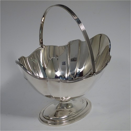 An Antique Sterling Silver sugar basket in a Georgian style, having a shaped oval body with panelled shoulders, an applied reeded border, a reeded swing-handle, and sitting on a pedestal foot. Made by Thomas Bradbury and Sons of Sheffield in 1913. The dimensions of this fine hand-made antique silver sugar basket are height 17 cms (6.75 inches), length 15 cms (6 inches), width 12.5 cms (5 inches), and it weighs approx. 231g (7.5 troy ounces).