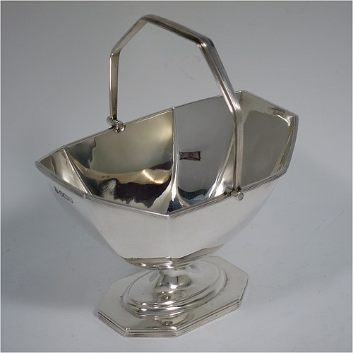An Antique Edwardian Sterling Silver sugar basket in a Georgian style, having a plain octagonal panelled shaped body, with applied reeded borders, a reeded swing-handle, and sitting on a pedestal foot. Made by Thomas Bradbury and Sons of Sheffield in 1907. The dimensions of this fine hand-made antique silver sugar basket are height 14.5 cms (5.75 inches), length 12.5 cms (5 inches), width 10 cms (4 inches), and it weighs approx. 170g (5.5 troy ounces).