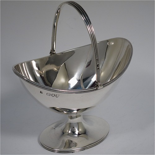 An Antique Victorian Sterling Silver sugar basket in a Georgian style, having a plain oval shaped body, with applied reeded borders, a reeded swing-handle, and sitting on a pedestal foot. Made by Holland, Aldwinckle, and Slater of London in 1895. The dimensions of this fine hand-made antique silver sugar basket are height 14.5 cms (5.75 inches), length 13 cms (5 inches), width 9.5 cms (3.75 inches), and it weighs approx. 188g (6 troy ounces).