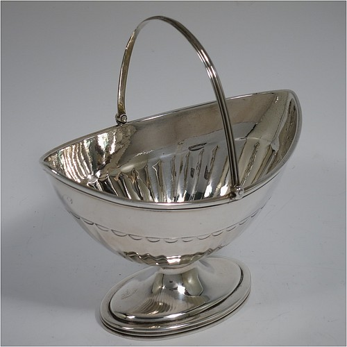 An Antique Georgian Sterling Silver sugar basket, having an oval bellied body with hand-chased half-fluting, with applied reeded borders, a hinged and reeded swing-handle, and sitting on a pedestal foot. Made by Peter & Anne Bateman of London in 1791. The dimensions of this fine hand-made antique silver sugar basket are height (inc. handle) 15 cms (6 inches), length 14 cms (5.5 inches), and it weighs approx. 198g (6.4 troy ounces).