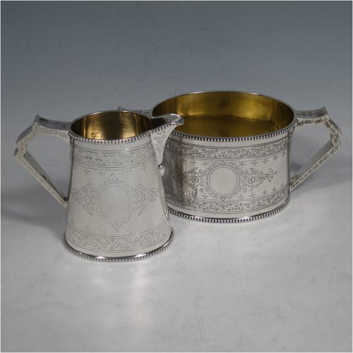 An Antique Victorian Sterling silver sugar and creamer set, having oval bodies with hand-engraved floral decoration, applied beaded borders, gold-gilt interiors, and angular handles. Made by Goldsmiths & Silversmiths of London in 1881. The dimensions of this fine hand-made antique silver cream and sugar set are height of creamer 9 cms (3.5 inches), length of sugar bowl 16 cms (6.25 inches), and with a total weight approx. 303g (9.8 troy ounces).