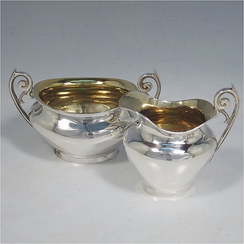 An Antique Edwardian Sterling Silver sugar and creamer set, having plain oval shaped bellied bodies, with gold-gilt interiors and scroll handles, and all sitting on flat bases. Made by Jones & Crompton of Birmingham in 1904. The dimensions of this fine hand-made antique silver tea set are length of sugar bowl 12 cms (4.75 inches), height 7.5 cms (3 inches), and the total weight is approx. 185g (6 troy ounces).