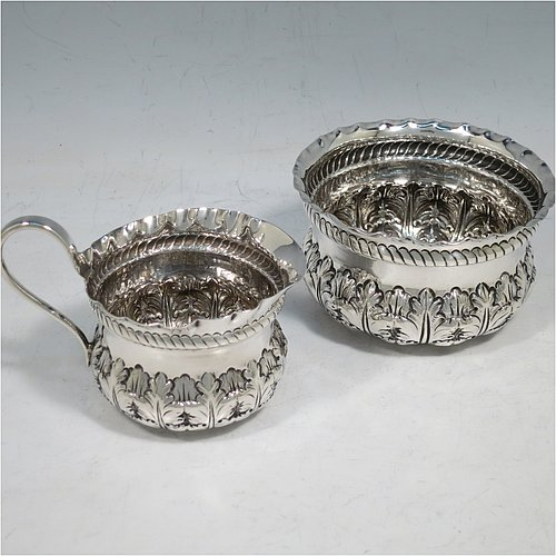 An Antique Victorian Sterling Silver sugar and creamer set, having round bodies with hand-chased floral decoration, with crimped borders above a band of rope-twist work, all sitting on flat bases. Made by George Maudsley Jackson of London in 1891. The dimensions of this fine hand-made antique silver sugar and creamer set are diameter of sugar bowl 9 cms (3.5 inches), height of cream jug 6 cms (2.5 inches), with a total weight of 108g (3.5 troy ounces).