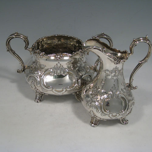 Antique Victorian sterling silver sugar and cream set, having round bellied hand-chased bodies with floral decoration, scroll handles, and sitting on scroll feet. Made by Martin Hall & Co., of Sheffield in 1856. The dimensions of this fine hand-made silver sugar and cream set are height of cream jug 16.5 cms (6.5 inches), width of sugar bowl 22 cms (8.6 inches), with a total weight of approx. 730g (23.5 troy ounces).