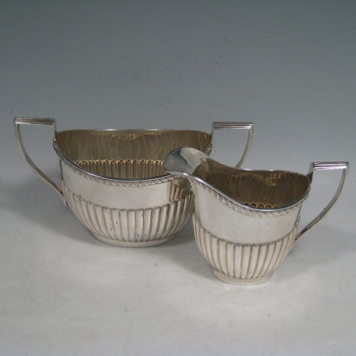 Antique Edwardian sterling silver sugar and creamer set, having oval bodies with hand-chased half-fluted decoration, applied gadroon borders, and reeded handles. Made by William Aitken of Birmingham in 1902. Height 10 cms (4 inches), length of sugar bowl 19 cms (7.5 inches). Total weight approx. 419g (13.5 troy ounces).