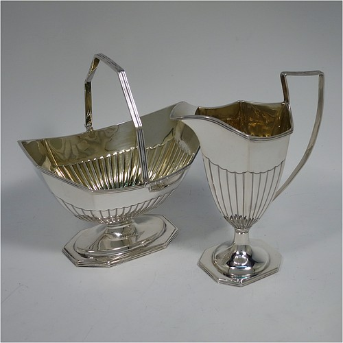 An Antique Victorian Sterling Silver sugar basket and cream jug set, having Neoclassical style panelled bodies with hand-chased half-fluted decoration, with applied reeded borders and gold-gilt interiors, the sugar basket with a swing-handle, and all sitting on pedestal feet. Made by Thomas Bradbury of London in 1897. The dimensions of this fine hand-made antique silver sugar and creamer set are height of cream jug 12.5 cms (5 inches), length of sugar basket 12.5 cms (5 inches), with a total weight of approx. 256g (8.3 troy ounces).
