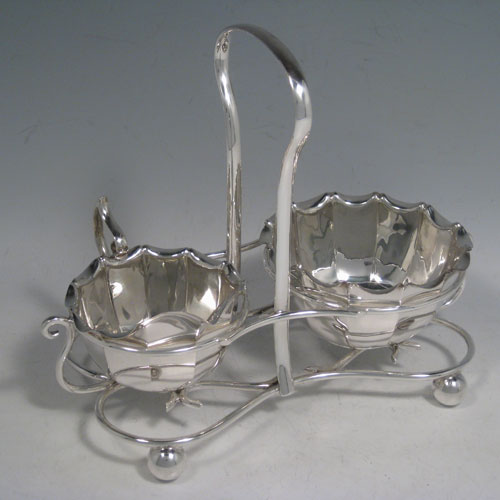 Sterling silver sugar and cream set in a frame, having round panelled bodies with scroll edges, and flat bases, all sitting in an original wire-work frame on four ball feet. Made by James Dixon and Sons of Sheffield in 1913. Height 18 cms (7 inches), length 22 cms (8.5 inches), width 12.5 cms (5 inches). Total weight 495g (16 troy ounces)