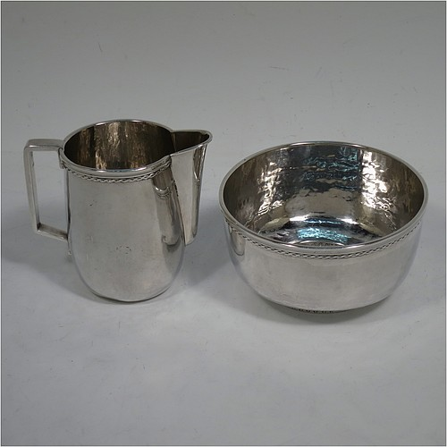A very attractive Arts and Crafts Sterling Silver sugar and creamer set, having round bodies with hand-hammered plenished decoration, with applied reeded and rope-twist top borders, all sitting on flat bases. Made by Edward Spencer of the Artificiers Guild of London in 1928. The dimensions of this fine hand-made Arts and Crafts  silver sugar and creamer set are diameter of sugar bowl 9 cms (3.5 inches), height of cream jug 7 cms (2.75 inches), with a total weight of 173g (5.6 troy ounces).