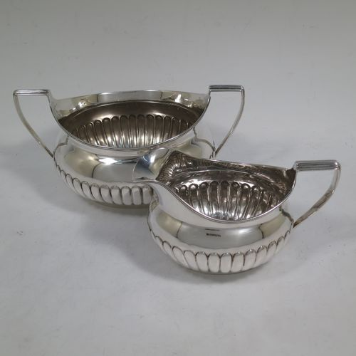 A very handsome Antique Georgian Irish Sterling Silver sugar bowl and cream jug set, having oval bellied bodies with hand-chased half-fluted decoration, applied reeded borders and flat-topped side-handles, and all sitting on collet feet. Made by James Scott of Dublin in 1806. The dimensions of this fine hand-made antique Irish silver sugar and creamer set are length of sugar bowl (inc. handles) 20 cms (8 inches), height 10 cms (4 inches), width 13 cms (5 inches), with a total weight of approx. 436g (14 troy ounces).