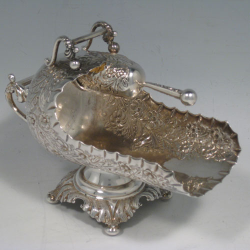 Antique Victorian sterling silver sugar scuttle, having a hand-chased body with floral decoration, two cast twin-scroll handles, an original scoop with gold-gilt interior, and sitting on a pedestal foot with four cushion feet. Made by Walker and Hall of Birmingham in 1899. Length 16 cms (6.25 inches), height 12.5 cms (5 inches), width 8 cms (3 inches). Weight approx. 216g (7 troy ounces).