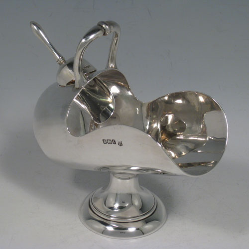 Antique Edwardian sterling silver sugar scuttle, having a plain body, a cast scroll handle, an original scoop, and sitting on a pedestal foot. Made by the Deakin Brothers of Sheffield in 1909. The dimensions of this fine hand-made silver sugar scuttle are length 16 cms (6.25 inches), height 14 cms (5.5 inches), width 7 cms (2.75 inches), and it weighs approx. 256g (8 troy ounces).