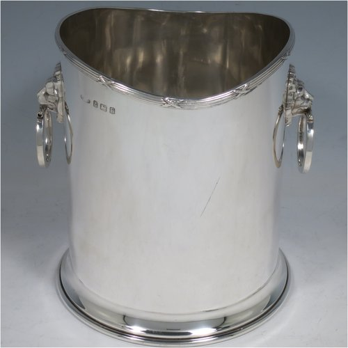 A Sterling Silver syphon stand, having a plain cylindrical body, two side-hinged ring handles with lion mask mounts, an applied reed and ribbon border, and sitting on a plain collet foot. Made by Britton, Gould & Co., of Birmingham in 1930. The dimensions of this fine hand-made silver siphon stand are diameter 13 cms (5 inches), height 14 cms (5.5 inches), and it weighs approx. 420g (13.5 troy ounces).