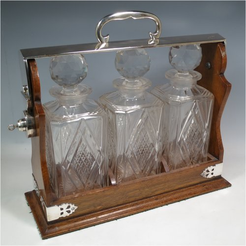An Antique Edwardian silver plated and wood-framed three bottle tantalus, with hand-cut crystal decanters and stoppers, all mounted in an oak frame with silver-plated swing handle, a patented lock mechanism, and hand-cut silver-plated mounts. Made in ca. 1905. The dimensions of this fine hand-made antique silver-plated and wooden framed tantalus are height 34 cms (13.5 inches), length , width 37 cms (14.5 inches), and width 14 cms (5.5 inches). Please note that shipping and insurance would be extra for this item so please check with us first before ordering.