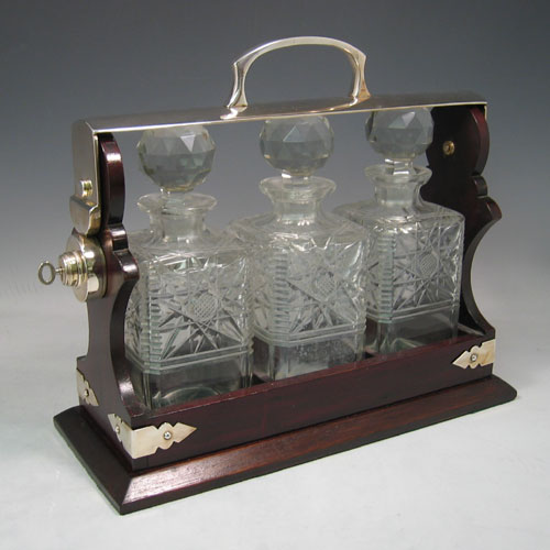 Antique Edwardian silver plated and wood-framed three bottle tantalus with hand-cut crystal decanters made in ca. 1910. Height 30 cms, width 35 cms.
