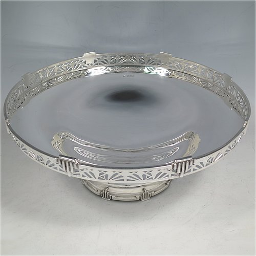 A Sterling Silver Art Deco tazza dish, having a round plain body, with a hand-pierced gallery border and applied Art Deco motifs, and all sitting on a matching pedestal foot. Made by Walker & Hall of Sheffield in 1933. The dimensions of this fine hand-made silver Art Deco tazza dish are height 10 cms (4 inches), diameter 25.5 cms (10 inches), and it weighs approx. 530g (17 troy ounces).