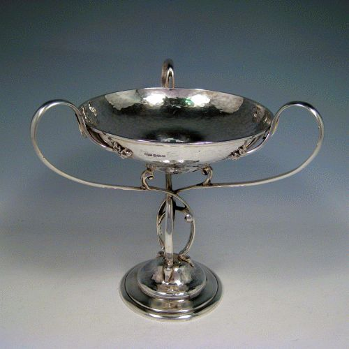 Sterling silver Arts & Crafts style hand-hammered tazza dish with three scroll handles, sitting on a pedestal foot above which the handles are inter-twined. Made by James Dixon of Sheffield in 1912. Height 21 cms (8.25 inches), diameter of bowl 16.5 cms (6.5 inches). Weight approx. 20.5 troy ounces (636g).