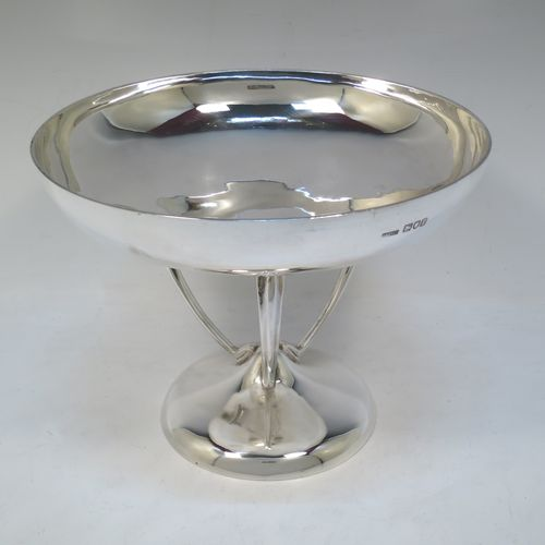 A pretty Art Nouveau style Antique Edwardian Sterling Silver tazza dish or bowl, having a plain round bowl body, sitting on a plain round pedestal foot with three scrolled supports. Made by Aspreys 