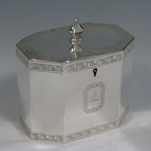 Antique Victorian sterling silver tea caddy box, having an octagonal straight-sided body, cast urn-shape finial sitting on a lid with flat hidden hinge, with hand-engraved neoclassical greek-key work, and an octagonal cartouche with crest. Made by John Edwards of London in 1854. Height 12 cms (4.75 inches), length 12 cms (4.75 inches), width 8 cms (3 inches). Weight approx. 449g (14.5 troy ounces).