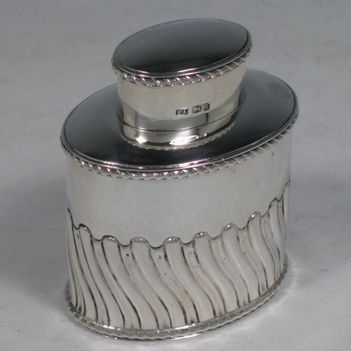 Antique Edwardian sterling silver tea caddy box, having an oval straight-sided body with hand-chased swirl-fluted decoration, applied gadroon borders, and a pull-off lid which was used as a measure. Made by Henry Atkins of Sheffield in 1908. The dimensions of this fine silver tea caddy box is height 8 cms (3 inches), length 6.5 cms (2.5 inches), width 4.5 cms (1.75 inches), and it weighs approx. 78g (2.4 troy ounces).