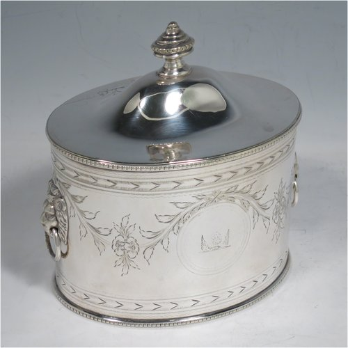 An Antique Victorian Silver Plated tea caddy box, in a neoclassical style having an oval straight-sided body, with cast lion-mask and ring handles, an urn-shaped finial sitting on a lid with flat hidden hinge, hand-engraved bands top and bottom, together with neoclassical style engraved swags, and with applied bead-edged borders. Made by Martin Hall & Co., in ca. 1880. The dimensions of this fine hand-made antique silver-plated tea caddy box are height 13 cms (5 inches), length 13 cms (5 inches), and width 9 cms (3.5 inches).