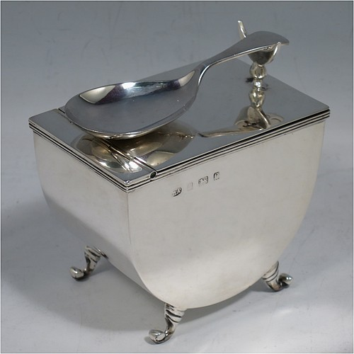 A very unusual Antique Edwardian Sterling Silver tea caddy box, having a plain U-shaped body with straight sides, a hinged lid with crescent shaped tea caddy spoon rest, a gold-gilt interior, and sitting on four cast scroll feet, together with a matching Old English pattern tea caddy spoon. Made by William Aitken of Birmingham in 1904 (the spoon made by Henry Atkins of Sheffield in 1918). The dimensions of this fine hand-made antique silver tea caddy box are height 7 cms (2.75 inches), length 9 cms (3.5 inches), width 6 cms (2.25 inches), and it weighs approx. 191g (6 troy ounces).