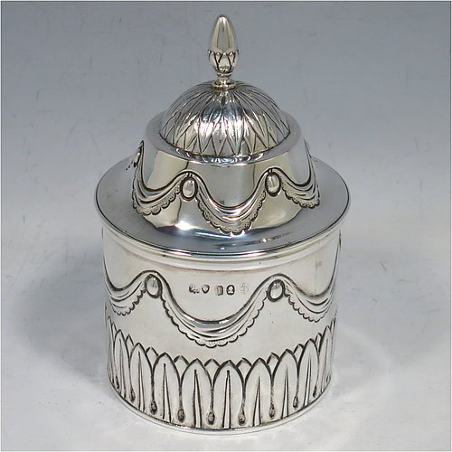 An Antique Georgian Sterling Silver tea caddy box, having a round straight-sided body with hand-chased Neoclassical style swags and anthemion leaves, with applied reeded borders, a pull-off domed lid with cast acorn finial, and all sitting on a flat base. Made by the Lias Brothers of London in 1826. The dimensions of this fine antique silver tea caddy box are height 12 cms (4.75 inches), diameter 7 cms (2.75 inches), and it weighs approx. 190g (6 troy ounces).