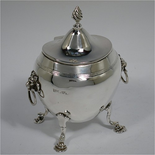 An Antique Edwardian Sterling Silver tea caddy box, having a plain oval bellied body with an upper band of hand-chased reeded decoration, a hinged lid with a cast swirl finial, with two cast lions-head ring side-handles, a gold-gilt interior, and sitting on four cast hoof feet with trefoil shoulders. Made by Nathan and Hayes of Chester in 1906. The dimensions of this fine hand-made antique silver tea caddy box are height 11.5 cms (4.5 inches), width 9 cms (3.5 inches), depth 6.5 cms (2.5 inches), and it weighs approx. 167g (5.4 troy ounces).