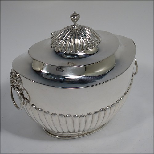 An Antique Edwardian Sterling Silver tea caddy box, having an oval bellied body with hand-chased half-fluted decoration, two lion-mask and ring side-handles, a hinged domed lid with matching fluting and a cast urn finial, and all sitting on a collet foot. Made by Goldsmiths and Silversmiths of London in 1906. The dimensions of this fine hand-made antique silver tea caddy box are height 11 cms (4.25 inches), length 12.5 cms (5 inches), width 8 cms (3.25 inches), and it weighs approx. 198g (6.4 troy ounces).