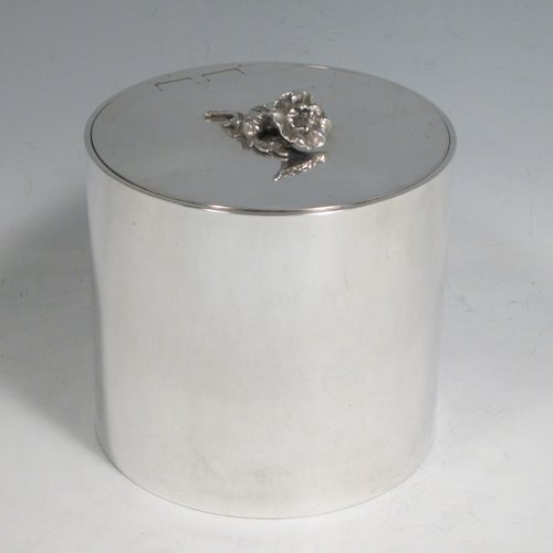 Sterling silver tea caddy box in a Georgian style, having a plain cylindrical body with straight sides, an invisibly hinged flat lid with floral finial, and sitting on a flat base. Made by Alston & Halom of London in 1918. The dimensions of this fine hand-made silver tea caddy box are height 10 cms (4 inches), diameter 11 cms (4.25 inches), and it weighs approx. 437g (14 troy ounces).