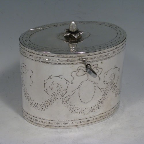 Antique Georgian sterling silver tea caddy box, having an oval straight-sided body, cast floral finial sitting on a lid with flat hidden hinge, hand-engraved bands top and bottom, together with neoclassical style engraved swags, and original lock with key. Made by Robert Hennell II of London in 1781. Height 11 cms (4.3 inches), length 12 cms (4.75 inches), width 8.5 cms (3.3 inches). Weight approx. 371g (12 troy ounces).