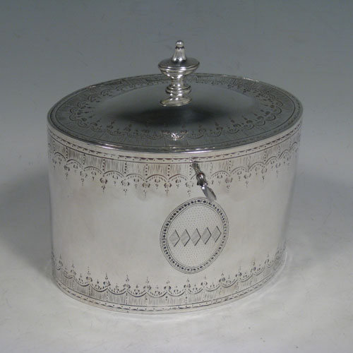 Antique Georgian sterling silver tea caddy box, having an oval straight-sided body, cast urn-shaped finial sitting on a lid with flat hidden hinge, hand-engraved bands of floral decoration top and bottom, together with two oval cartouches front and back, and original lock with key. Made by Robert Sharp of London in 1788. Height 14 cms (5.5 inches), length 13.5 cms (5.25 inches), width 9 cms (3.5 inches). Weight approx. 414g (13.4 troy ounces). Please note that this item is crested.