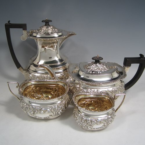 Antique Edwardian sterling silver four-piece tea and coffee set, having rectangular baluster bodies with rounded corners, with hand-chased floral decoration, and wooden handles and finials, the sugar bowl and cream jug with gold-gilt interiors, and all sitting on flat bases. Made by W. G. Knight of Birmingham in 1909. The dimensions of this fine hand-made silver tea and coffee service are length of teapot 32 cms (12.5 inches), height of hot-water pot 23 cms (9 inches), and the total weight is approx. 1,640g (53 troy ounces).