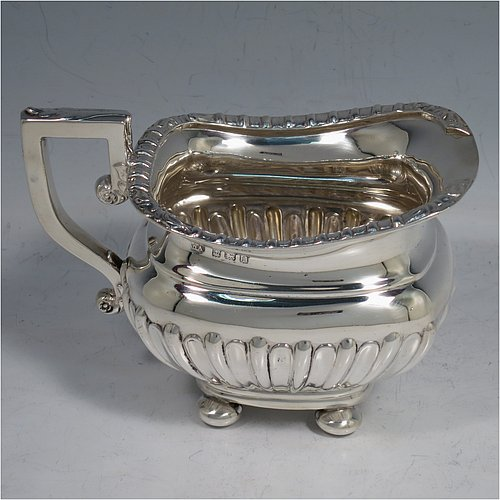 An Antique Edwardian Sterling Silver four-piece tea and coffee set in a Regency style, having rectangular baluster bodies, with hand-chased half-fluted decoration and applied gadroon borders, with insulated silver handles and bone finials, all sitting on four round cushion feet. Made by William Aitken of Birmingham in 1908. The dimensions of this fine hand-made silver tea and coffee service are length of teapot 26 cms (10.25 inches), height of coffee pot 23 cms (9 inches), and the total weight is approx. 1,760g (56.8 troy ounces).