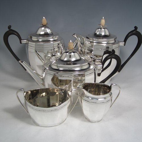 Sterling silver Georgian style five-piece tea and coffee service, consisting of teapot, coffee pot, hot water pot, sugar bowl and cream jug. Having oval panelled bodies with a band of floral decoration, with wooden handles and ivory pineapple shaped finials, and sitting on flat bases. Made by Roberts & Belk of Sheffield in 1919. The dimensions of this fine hand-made tea and coffee service are length of teapot 27 cms (10.5 inches), height of coffee pot 22 cms (8.75 inches), and the total weight is approx. 1,800g (58 troy ounces).