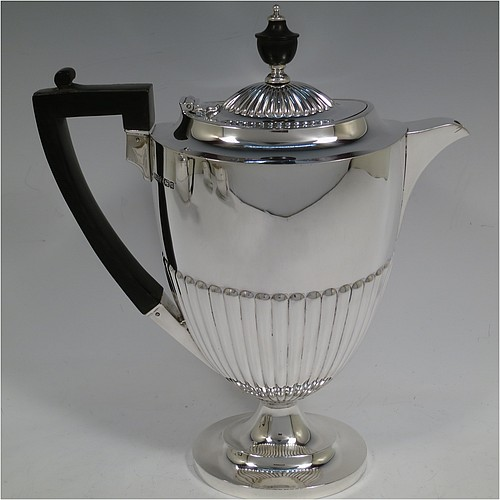 A very handsome Antique Edwardian Sterling Silver Queen Anne style four-piece tea and coffee set consisting of a coffee pot, tea-pot, sugar bowl, and milk / cream jug, having oval bodies with hand-chased half-fluted decoration, with wooden handles and finials, and all sitting on pedestal and collet feet. All made by Roberts and Belk of Sheffield in 1907/10. The dimensions of this fine hand-made antique silver tea and coffee service are length of teapot 26.5 cms (10.5 inches), height of coffee pot 26 cms (10.25 inches), and the total weight is approx. 1,350g (42 troy ounces).