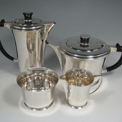 Sterling silver Art Deco style four-piece tea and coffee service, having plain round tapering bodies, with wooden handles and finials, and sitting on collet feet. Made by Hukin & Heath of Birmingham in 1938. The dimensions of this fine hand-made tea snd coffee service are length of teapot 23 cms (9 inches), height of coffee pot 20 cms (8 inches), and the total weight is approx. 1,426g (46 troy ounces).