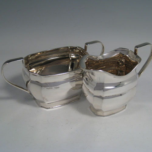 Sterling silver four-piece tea and coffee set, having plain panelled baluster bodies, and wooden handles and finials, all sitting on flat bases. Made by Harrison Fisher and Co., of Sheffield in 1947. The dimesions of this fine hand-made silver tea and coffee service are length of teapot 27 cms (10.5 inches), height of hot-water pot 23 cms (9 inches), and the total weight is approx. 52 troy ounces (1,612g).
