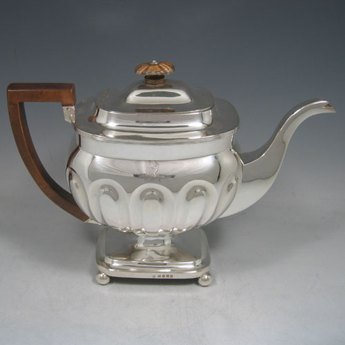 Antique Georgian sterling silver four-piece tea and coffee service, consisting of a coffee pot, tea pot, sugar bowl, and cream jug, having melon fluted bodies, gold gilt interiors, hinged lids with wooden finials, and insulated wooden handles, all sitting on four ball feet. Made by Henry Nutting and Robert Hennell II of London in 1808. Height of coffee pot 21.5 cms (8.5 inches), length of teapot 27 cms (10.5 inches). Total weight approx. 1,800g (58 troy ounces). Please note that all items are part-crested.