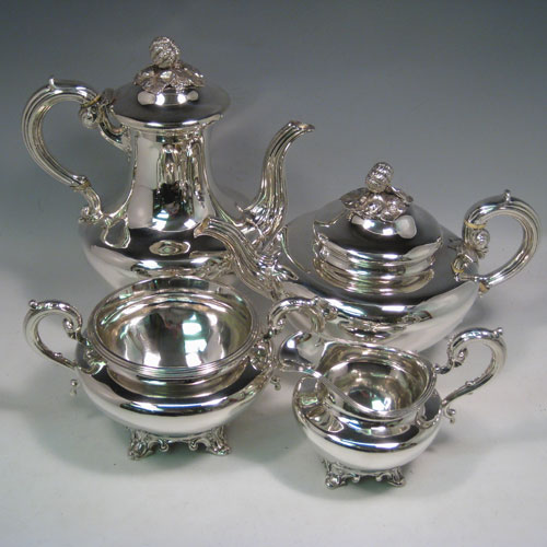 Antique Victorian sterling silver four-piece tea and coffee service, consisting of a coffee pot, tea pot, sugar bowl, and cream jug, having plain round baluster, hinged lids with floral finials, and insulated silver handles, and sitting on four floral feet. Made by the Savory Brothers of London between 1848 and 1854. Height of coffee pot 25.5 cms (10 inches), length of teapot 29 cms (11.5 inches). Total weight approx. 2,138g (70 troy ounces).