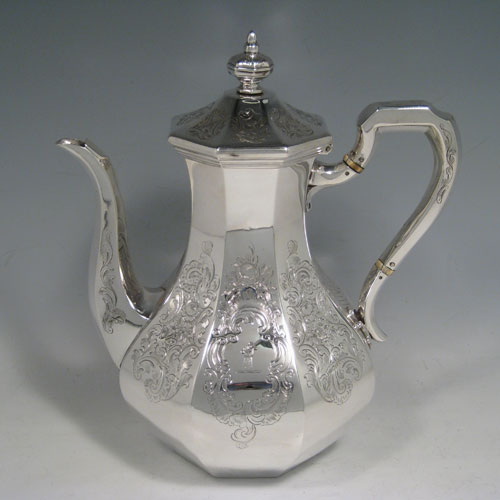 Antique Victorian sterling silver four-piece tea and coffee service, consisting of a coffee pot, tea pot, sugar bowl, and cream jug, having octagonal panelled bodies with hand-engraved floral decoration, hinged lids with finials, and insulated silver handles. Made by William Kerr Reid of London in 1850. Height of coffee pot 25 cms (10 inches), length of teapot 23.5 cms (9.25 inches). Total weight approx. 1,740g (56 troy ounces).